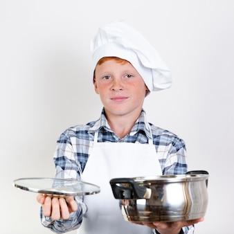 Vista frontal bonito jovem garoto segurando pan