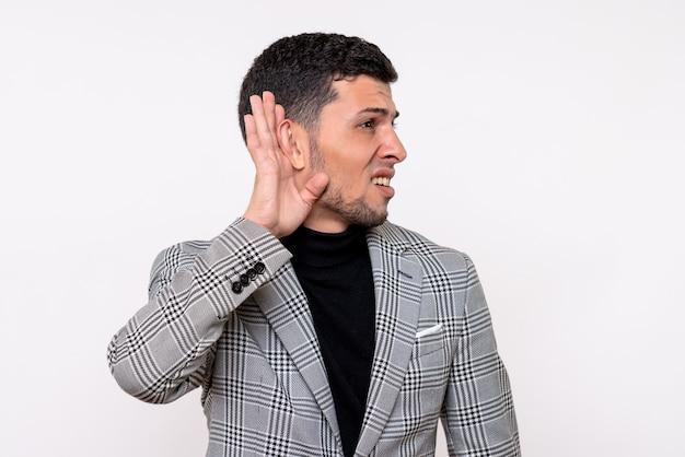 Vista frontal bonito jovem homem de terno ouvindo algo em pé sobre fundo branco