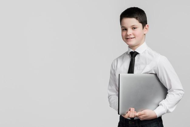 Vista frontal bonito menino segurando laptop