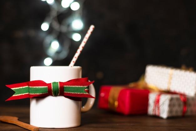 Vista frontal branca xícara de chá com luzes de natal em segundo plano