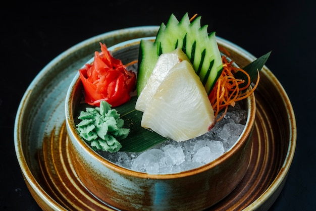 Vista frontal branco peixe fumado balyk com pepino picado wasabi e gengibre no gelo