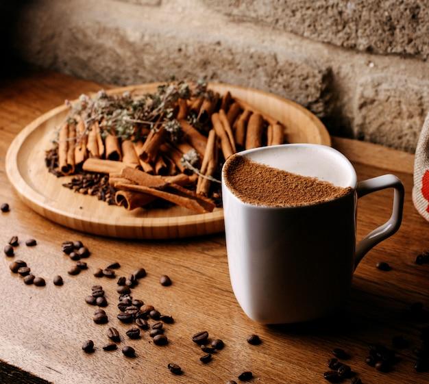 Vista frontal café dentro de copo branco, juntamente com sementes de café e canela