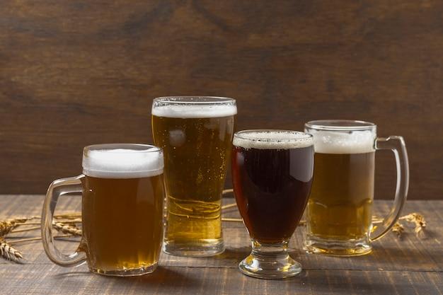 Vista frontal caneca e copos com cerveja na mesa
