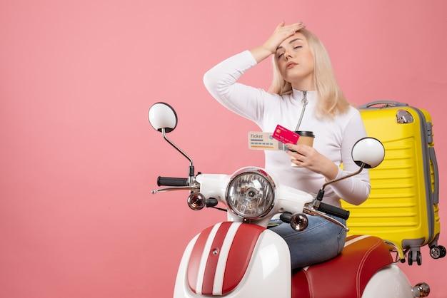 Vista frontal cansada jovem em ciclomotor colocando a mão na cabeça segurando a xícara de café