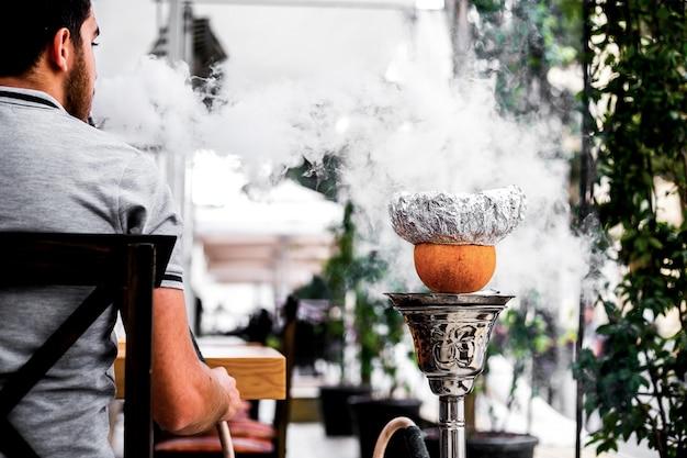 Vista frontal cara fuma shisha com uma laranja