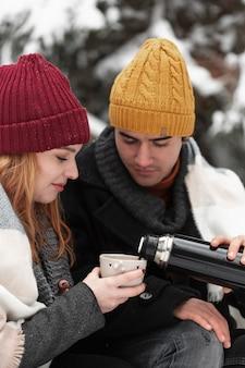 Vista frontal casal com roupas de inverno, derramando bebida quente