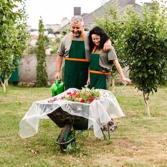 Vista frontal casal feliz com carrinho de mão