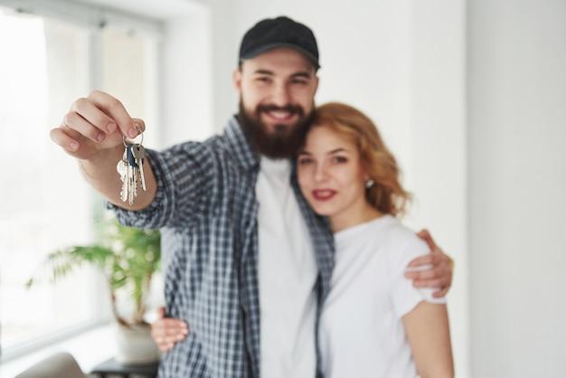 Vista frontal. casal feliz juntos em sua nova casa. concepção de movimento