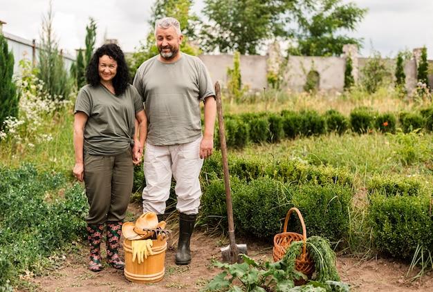 Vista frontal casal sênior com acessórios de jardinagem