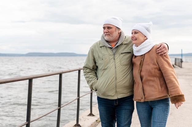 Vista frontal casal sênior na beira-mar