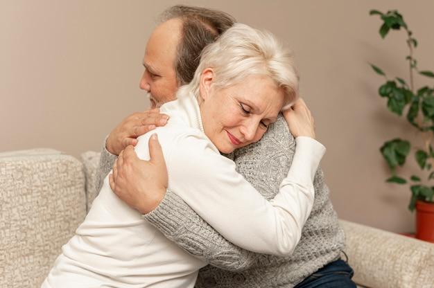 Vista frontal casal sênior no sofá abraçando