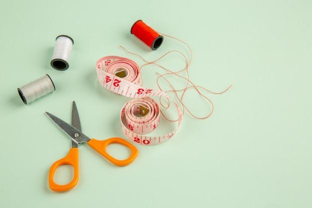 Vista frontal centímetro rosa com tesoura em uma superfície verde agulhas costurando fotos roupas com alfinetes costurar