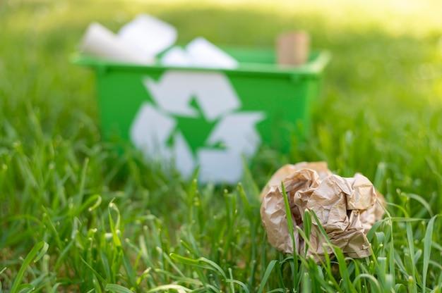 Vista frontal, cesta de reciclagem na grama com lixo