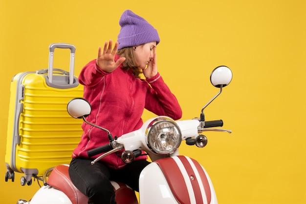 Vista frontal chateada jovem em ciclomotor fazendo sinal de pare