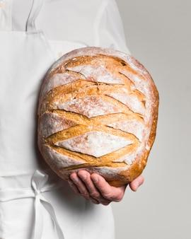 Vista frontal chef vestindo roupas brancas, segurando um pão