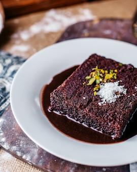 Vista frontal choco bolo saboroso doce dentro de chapa branca em cima da mesa marrom