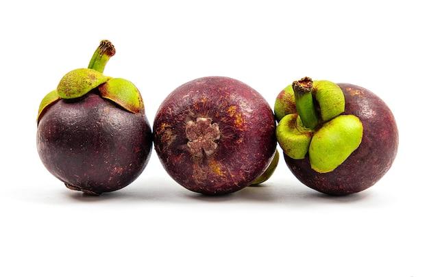 Vista frontal close de muitos frutos frescos do mangostão colocados no branco