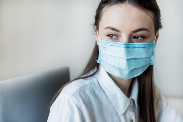 Vista frontal close-up de um profissional de saúde feminina vestindo máscaras cirúrgicas em um hospital. profissionais de saúde na pandemia de coronavirus covid19