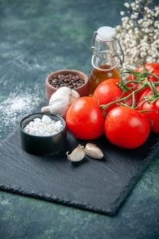 Vista frontal close-up tomates vermelhos frescos com temperos na superfície escura refeição comida saúde dieta salada