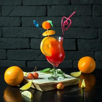 Vista frontal cocktail onn livro aberto com uma fatia de laranja em forma de uma decoração