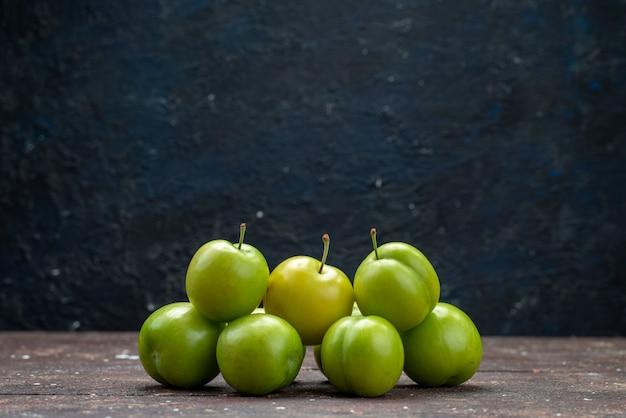Vista frontal com ameixas verdes amargas forradas de madeira fresca