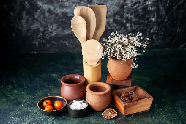 Vista frontal com colheres de madeira com potes e canela na mesa escura. foto colorida tempero talheres de sal
