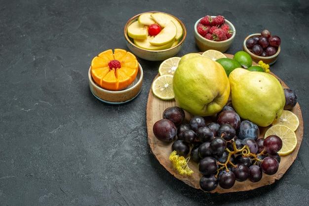Vista frontal com composição de frutas diferentes frescas e maduras em fundo cinza escuro frutas maduras planta saudável cor suave