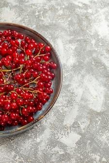Vista frontal com cranberries vermelhas frescas dentro da bandeja na mesa branca cor de frutas vermelhas silvestres