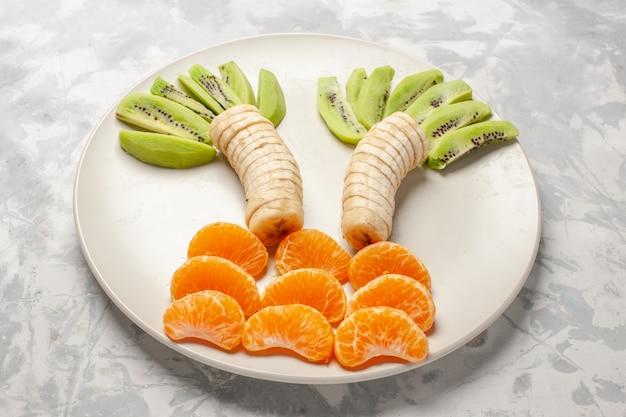 Vista frontal com frutas fatiadas, kiwis, bananas e tangerinas na superfície branca frutas exóticas tropicais frescas maduras