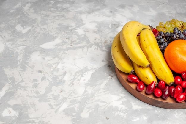 Vista frontal composição de frutas bananas dogwoods e uvas em fundo branco claro frutas baga frescor vitamina cor
