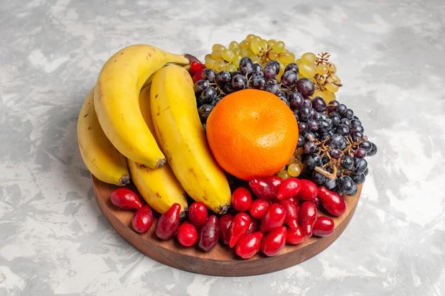 Vista frontal composição de frutas bananas dogwoods e uvas na superfície branca fruta baga frescura composição cor vitamínica