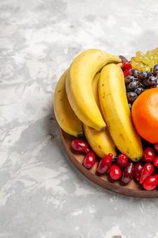 Vista frontal composição de frutas bananas dogwoods e uvas na superfície branca frutas baga frescor vitamina Foto gratuita