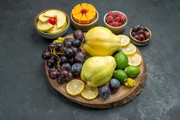 Vista frontal, composição de frutas diferentes frescas e maduras em fundo cinza escuro frutas maduras maduras saúde planta cor