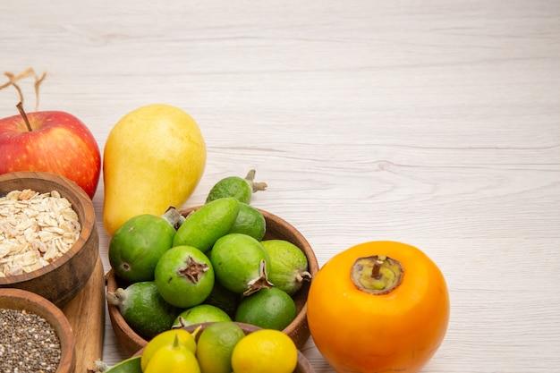 Vista frontal composição de frutas frescas diferentes frutas em fundo branco frutas cítricas cor baga madura saborosa dieta exótica