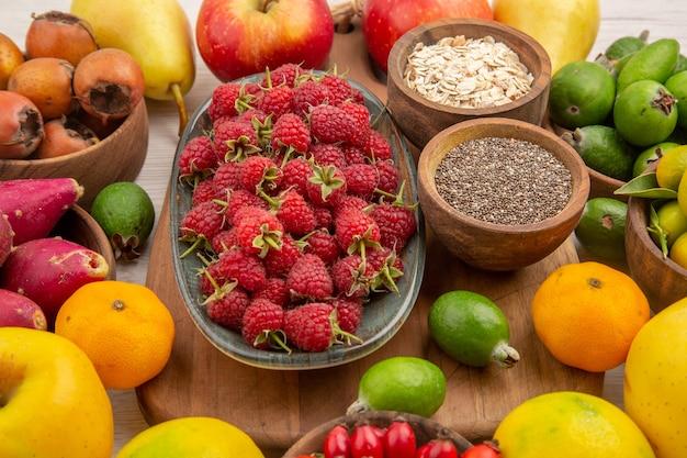 Vista frontal composição de frutas frescas frutas diferentes em fundo branco saúde frutas cítricas cor baga madura saborosa dieta exótica