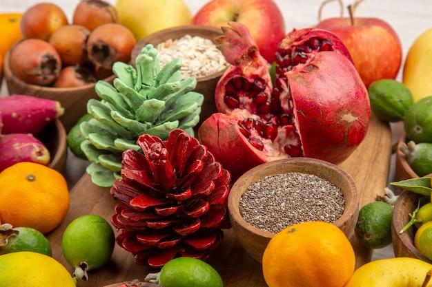 Vista frontal composição de frutas frescas frutas diferentes em fundo branco saúde frutas cítricas cor baga madura saborosa