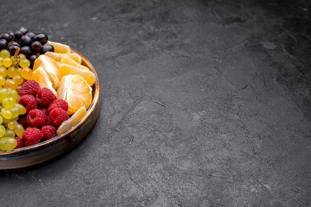 Vista frontal composição de frutas morangos uvas framboesas e tangerinas dentro da bandeja no espaço escuro