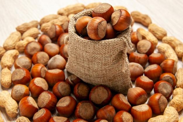 Vista frontal composição de nozes frescas avelãs e amendoins na mesa branca, porca lanche amendoim noz