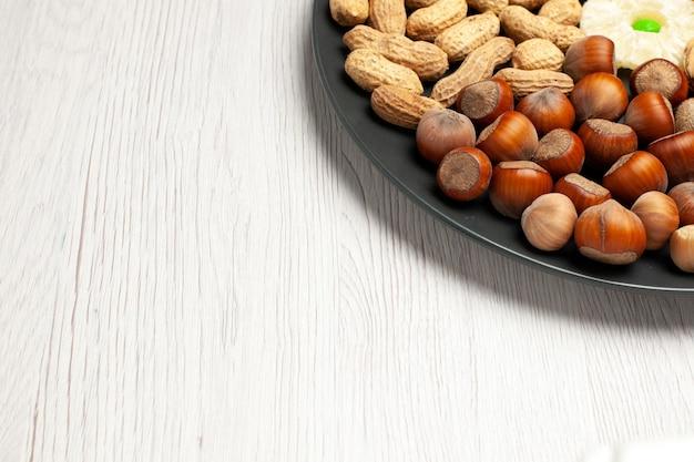 Vista frontal composição de nozes nozes frescas amendoim e avelãs dentro da placa na mesa branca nozes árvore lanche planta muitos shell