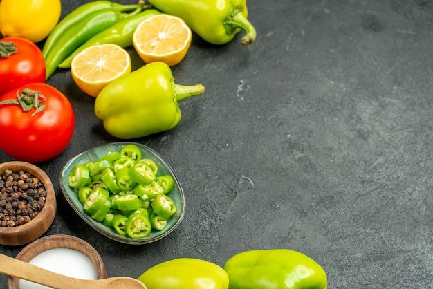 Vista frontal composição de vegetais tomates pimentões e limão em um fundo escuro refeição salada dieta saudável alimentos