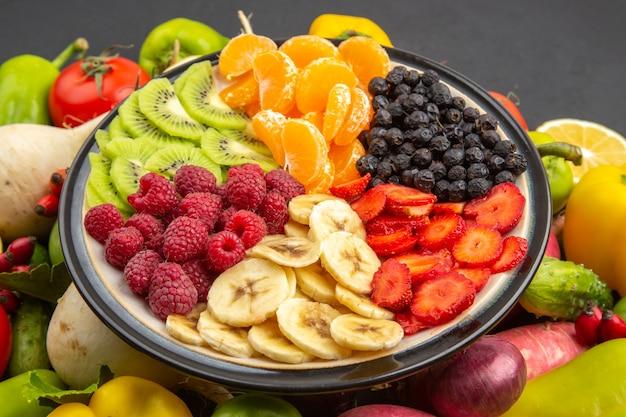 Vista frontal composição vegetal legumes frescos com frutas fatiadas no escuro vida saudável planta dieta madura comida salada cor