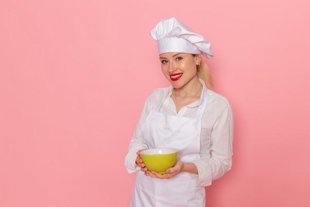 Vista frontal, confeiteira feminina vestida de branco segurando um prato verde na parede rosa comida refeição sopa verduras vegetais