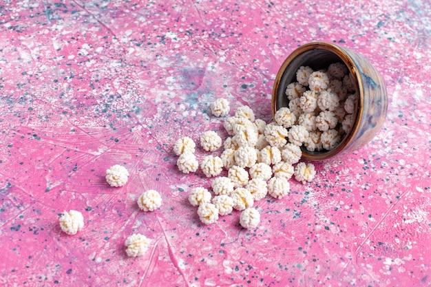 Vista frontal confitures doces brancos na superfície rosa