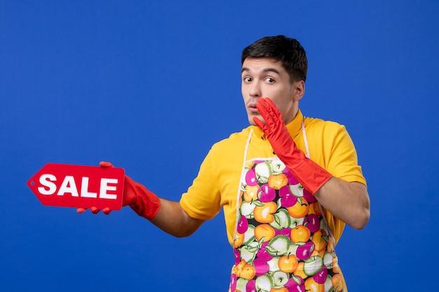 Vista frontal confusa empregada masculina com camiseta amarela segurando uma placa de venda e dizendo algo no espaço azul
