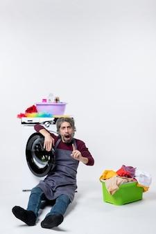 Vista frontal confusa empregada masculina sentada em frente ao cesto de roupa suja da máquina de lavar no fundo branco
