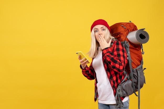 Vista frontal confusa garota loira com sua mochila segurando um cartão