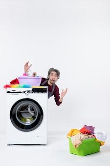 Vista frontal confusa governanta masculina com avental sentada atrás do cesto de roupa suja da máquina de lavar no fundo branco isolado