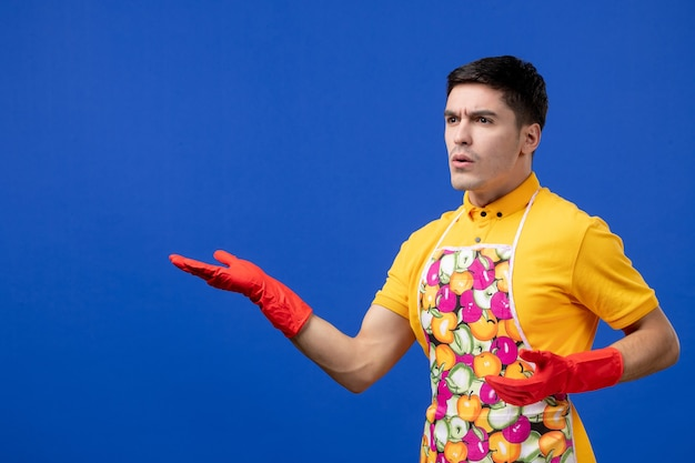 Vista frontal confusa governanta masculina de avental abrindo as mãos