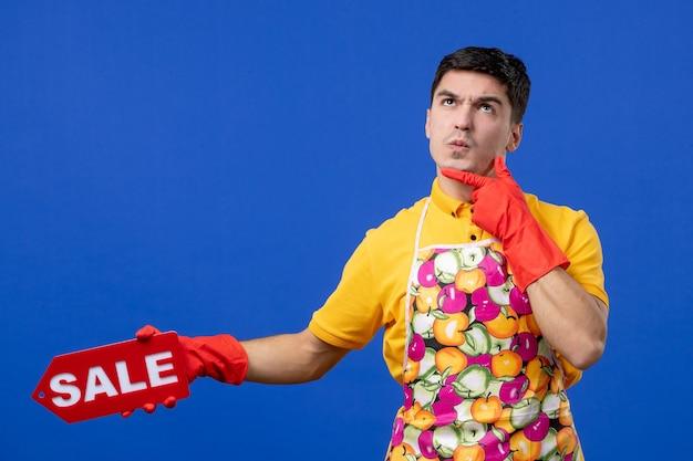 Vista frontal confusa governanta masculina em camiseta amarela segurando uma placa de venda e colocando a mão em seu queixo no espaço azul