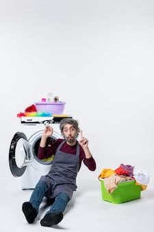 Vista frontal confusa governanta masculina sentada em frente ao cesto de roupa suja da máquina de lavar no fundo branco